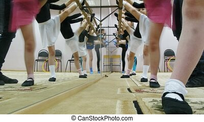 Group of girls stretching legs during dancing classes -...