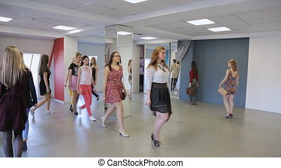 Group of girls trains in defile in dancing class. They move...