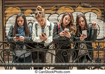 Group of girls using cellphones. Technology isolation and...