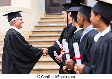 group of graduates in line handshaking with dean