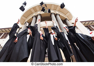 group of graduates throwing graduation hats in the air -...