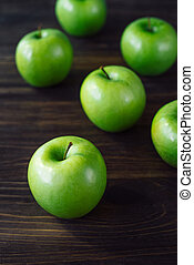 Group of green apples on brown wooden background.