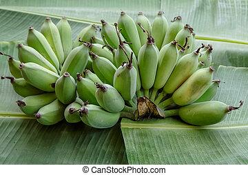 group of green banana on banana leaf background