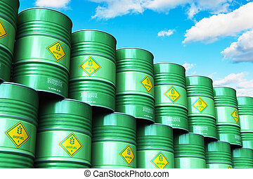 Group of green stacked biofuel drums against blue sky with clouds