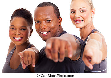 group of gym instructors pointing at the camera - smiling...