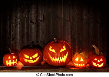 Group of Halloween Jack o Lanterns at night with a rustic dark wooden background