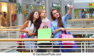 Group of happy best friends with shopping bags taking a selfie in the city. Slow motion.