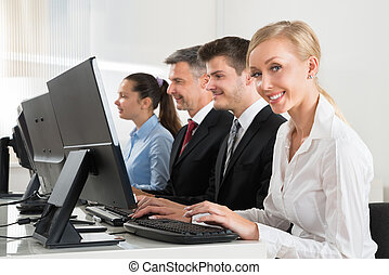 Businesspeople Working On Computers At Desk