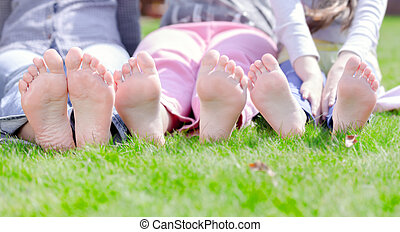 Group of happy children lying on green grass in park