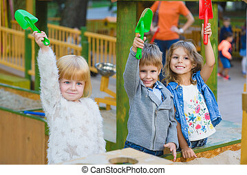 group of happy children playing in sandbox at playground