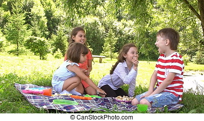 Group of happy children playing outdoors in summer park. Slow motion
