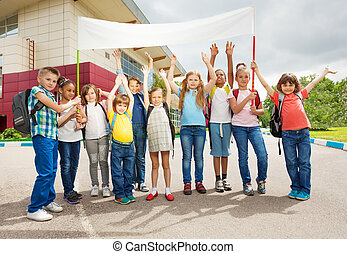 Group of happy children with arms up hold placard