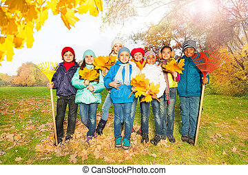 Group of happy children with rakes and leaves