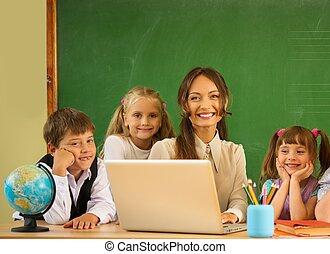 Group of happy classmates with their teacher in class near blackboard