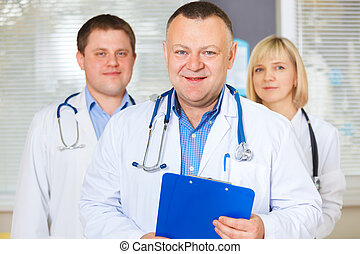 Group of happy doctors looking at camera.