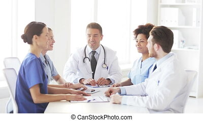 group of happy doctors making high five at clinic
