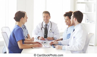 group of happy doctors with hands on top at clinic