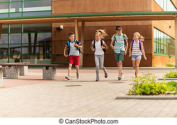 group of happy elementary school students running