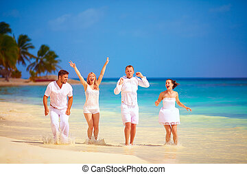 group of happy excited friends having fun on tropical beach, summer vacation