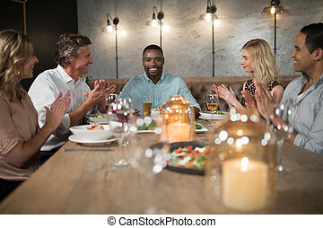 Group of happy friends applauding man while dining