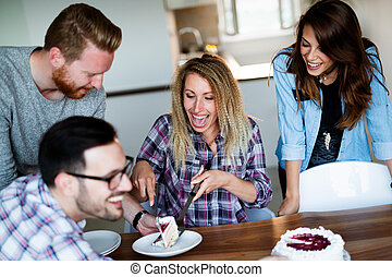 Group of happy friends celebrating birthday at home together