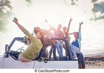 Group of happy friends having fun on convertible car in vacation - Young people drinking champagne and taking selfie during their road trip - Travel, friendship, youth lifestyle holidays concept