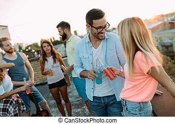 Group of happy friends having party on rooftop - Group of ...