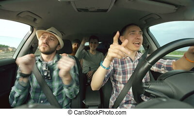 Group of happy friends in car singing and dancing while...