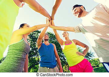 group of happy friends making high five outdoors