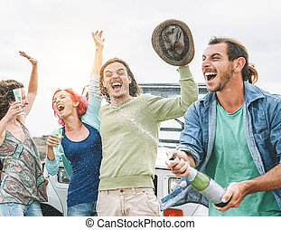 Group of happy friends making party with a bottle of champagne - Travel people having fun celebrating during their road trip with convertible car - Friendship, vacation, youth holidays lifestyle concept