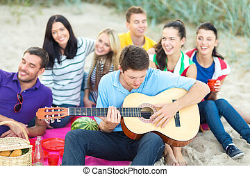 group of happy friends playing guitar on beach