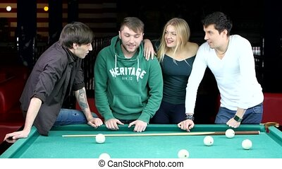 Group of happy friends playing in billiard. Company of three boys and one girl