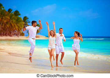 group of happy friends running on tropical beach, summer vacation