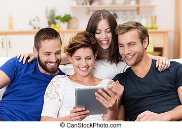 Group of happy friends sharing a tablet