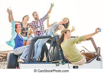 Group of happy friends taking selfie with mobile smart phone on convertible car - Young people having fun making party during their road trip - Friendship, vacation, youth holidays lifestyle concept