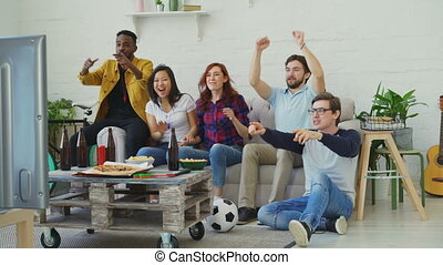 Group of happy friends watching sports game on TV at home....