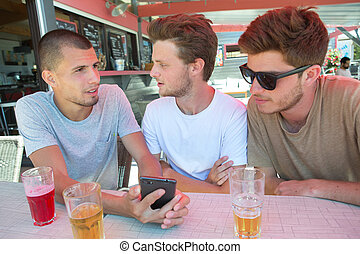 group of happy friends with smartphones and drinks at bar