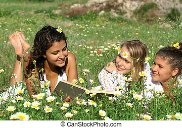 group of happy healthy people reading outdoors
