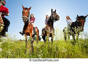 Group of happy horse riders in flowery meadow