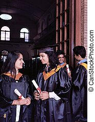 Group of happy Indian students in their graduation dress, smiling with their degree.