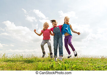 group of happy kids jumping high on green field