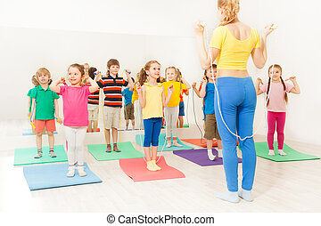 Group of happy kids jumping ropes at gym lesson