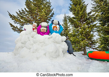 Group of happy kids play snowballs game together