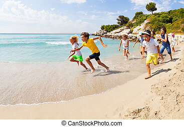 Group of happy kids racing on sandy beach