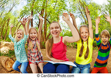 Group of happy kids reading a book in summer park
