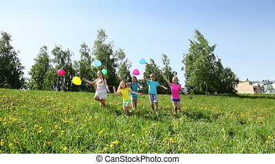 Group of happy kids run with balloons having happy party in the spring sunny day on dandelion filed