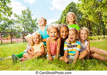 Group of happy little kids on the lawn in park