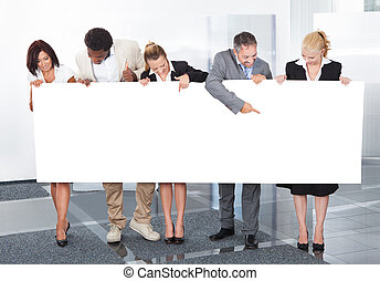 Group Of Happy Multiracial Businesspeople Holding Placard In Office