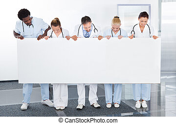 Group Of Happy Multiracial Doctors Holding Placard In Clinic