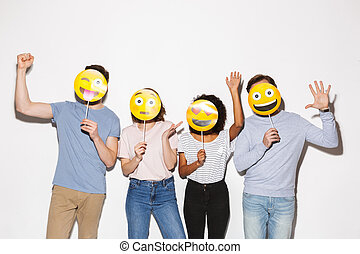 Group of happy multiracial people holding smiley faces